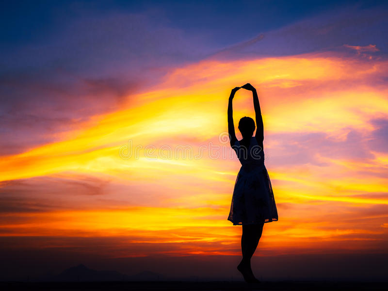 Relaxing woman at sunset. Silhouette of free woman enjoying freedom feeling happy at sunset. relaxing woman in pure happiness stock photo