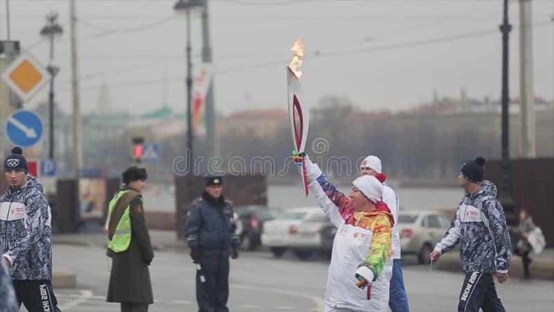 Relay race Olympic flame in Saint Petersburg in October  Walking woman  torchbearer  Guards