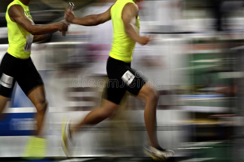 Relay Race Running as Team Towards Victory and Success with Baton stock image