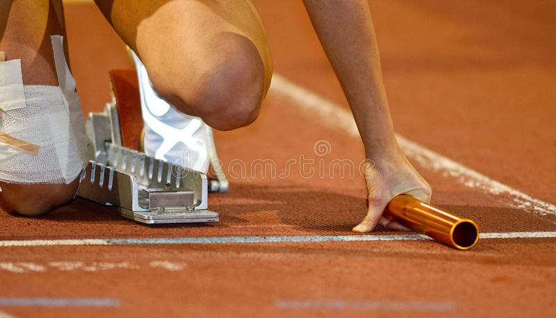 Relay runner in the starting blocks royalty free stock photography