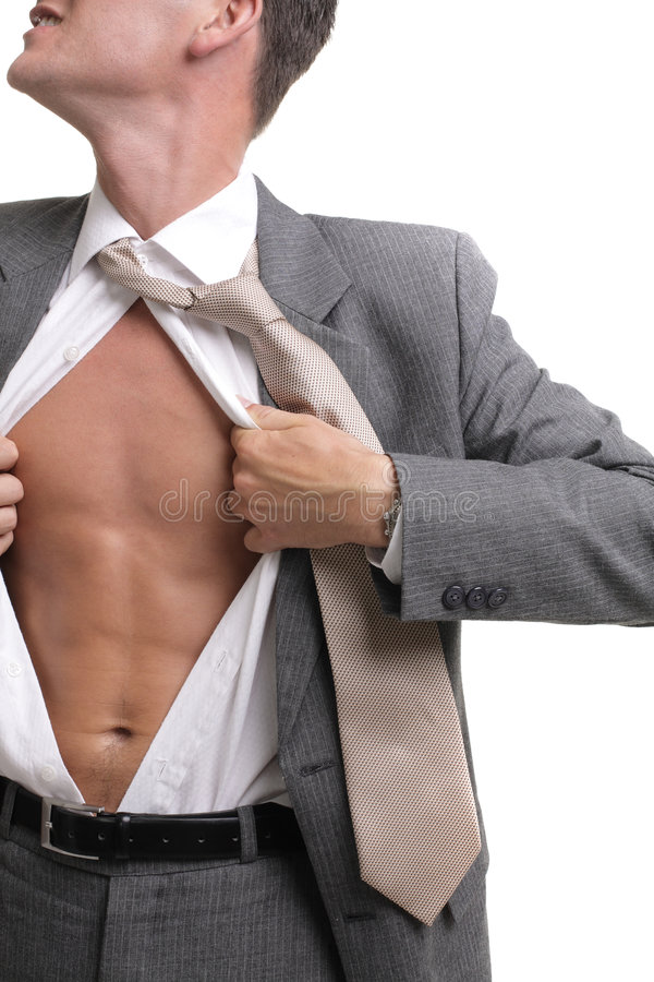 Release!. Young businessman dressed in suit, shirt and tie pulling his shirt open revealing well-built torso stock image