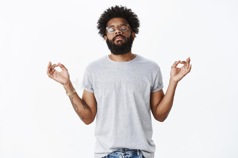 Releasing pressure with meditation. Portrait of calm and peaceful adult african american bearded man with tattoos and royalty free stock image