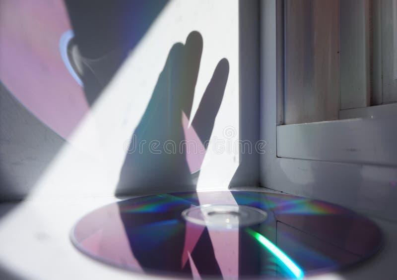 Relfection do CD com mão e luzes imagem de stock