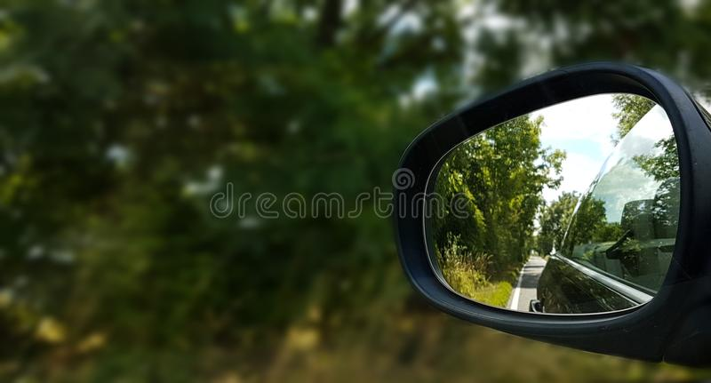Relflection da estrada e das árvores no wingmirror do carro fotos de stock royalty free