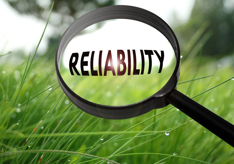 Reliability. Magnifying glass with the word reliability on grass background. Selective focus stock images