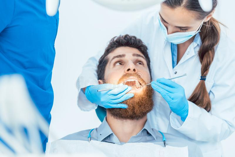 Reliable dentist using sterile instruments while cleaning the te stock photos