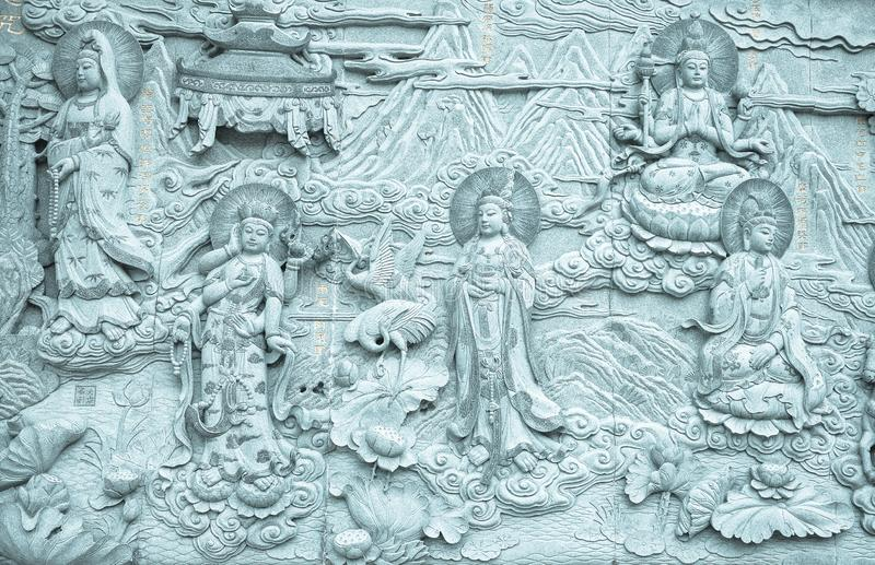 Relief stone carving on wall about Buddha in Buddhist temple royalty free stock photo