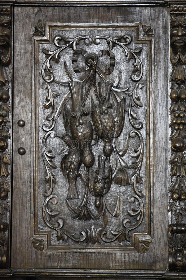 Relief wildfowl carved. Oak panel old cupboard royalty free stock images