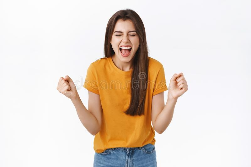 Relieved, happy woman rejoicing in yellow t-shirt, clench fists and smiling joyfully, achieve success, got lucky winning. Prize, become champion, close eyes and royalty free stock images