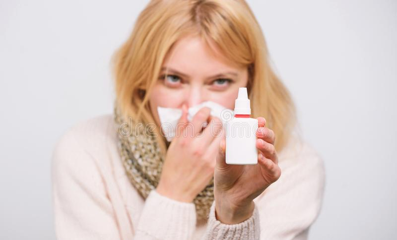 Relieving itchy nose. Cute woman nursing nasal cold or allergy. Sick woman spraying medication into nose. Treating. Common cold or allergic rhinitis. Unhealthy stock photos