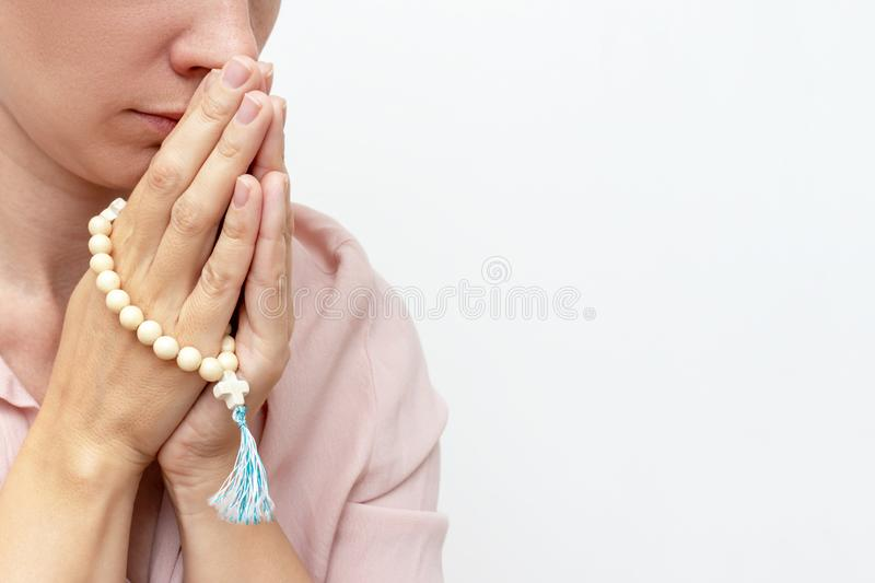 Religeous caucasian young woman praying and holding rosary in hands on white background, copy space.  stock photography