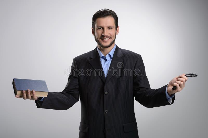 Religiös affärsman. Gladlynt skäggig man i formalwearholdin royaltyfria bilder
