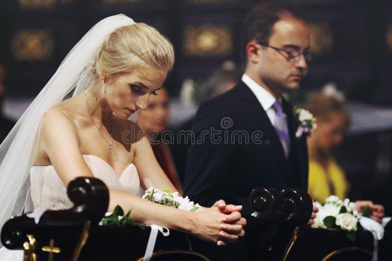 Religiös brud och brudgum som ber i kyrka på bröllopceremoni royaltyfri fotografi