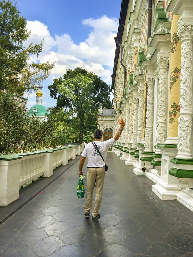 Religiös man på matsalkyrkaterrassen med handen som springas upp i helig Treenighet - St Sergius Lavra fotografering för bildbyråer