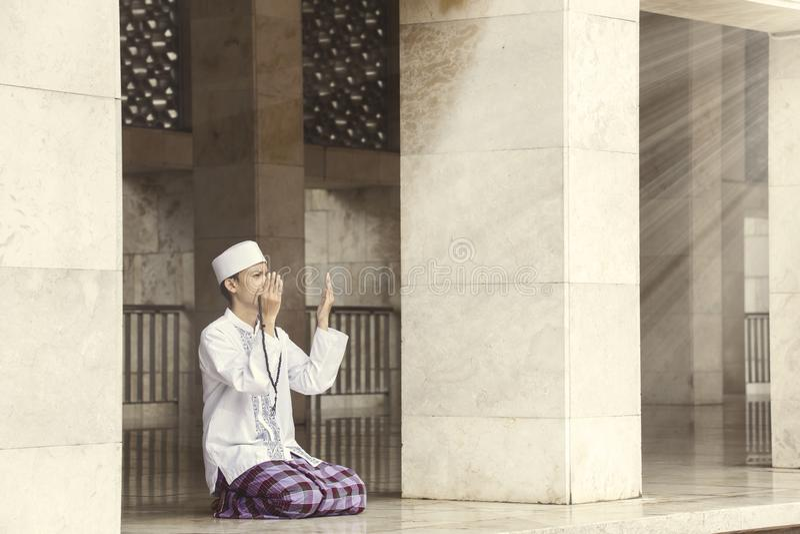 Religiös muslimsk man som ber till Allahen royaltyfri fotografi