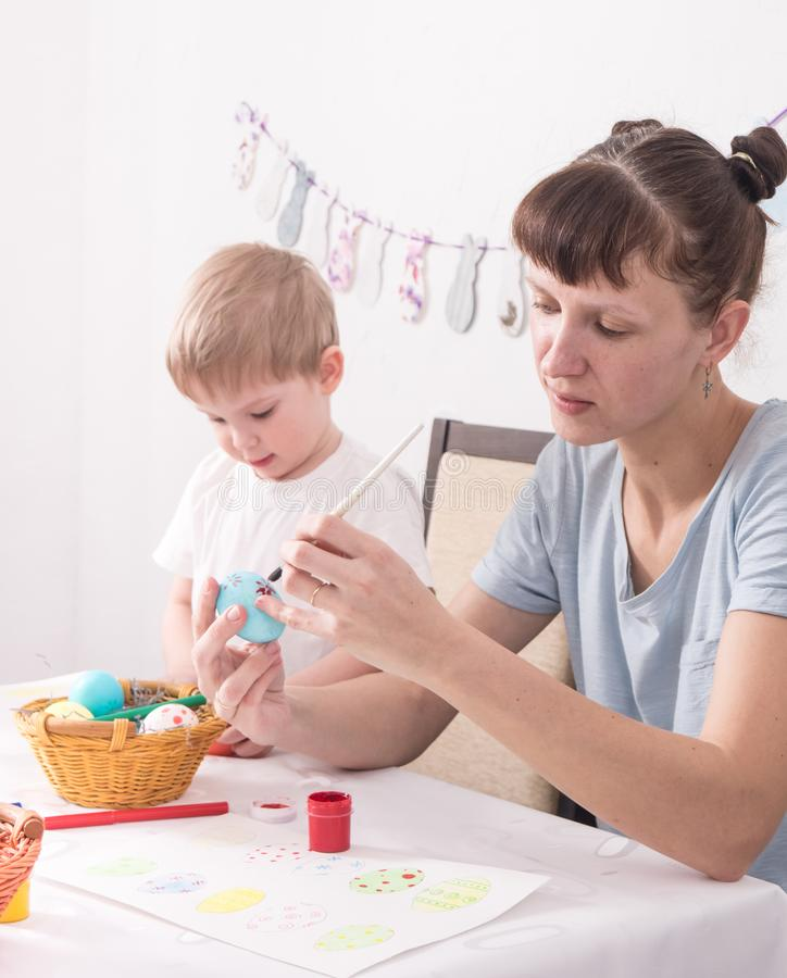 Religiösa ferier: Ägg för mamma- och sonmålarfärgpåsk arkivfoton