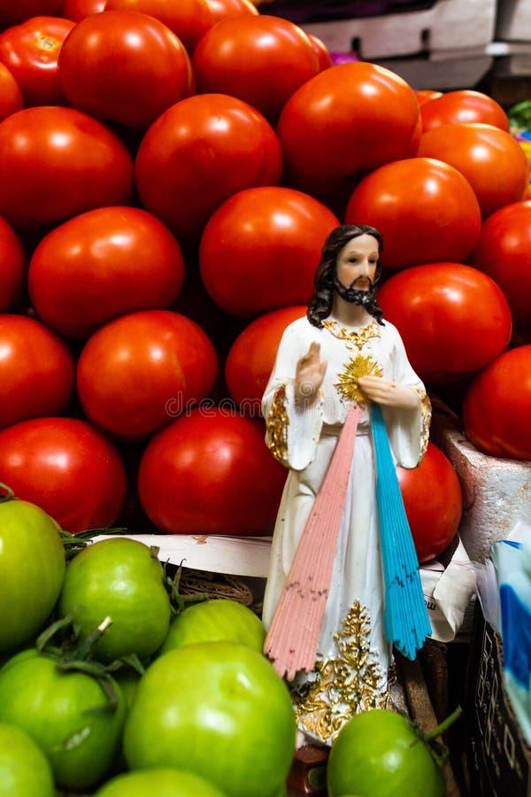 Religiöse Figur mitten in den roten und grünen Tomaten an einem Marktstall lizenzfreie stockfotografie