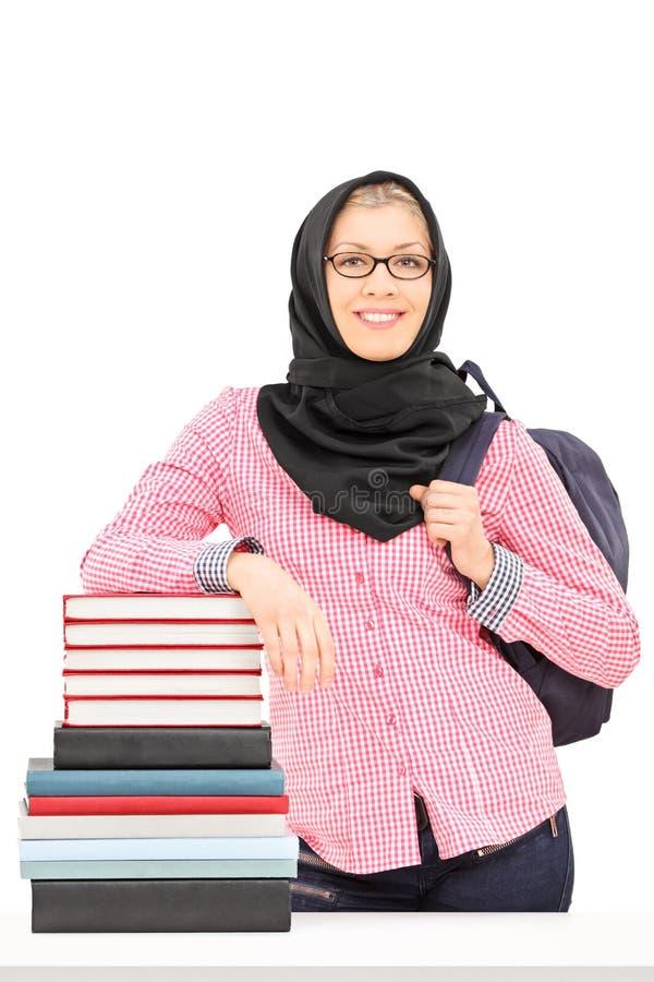 Religiöse Studentin, die auf Stapel Büchern sich lehnt stockfotos
