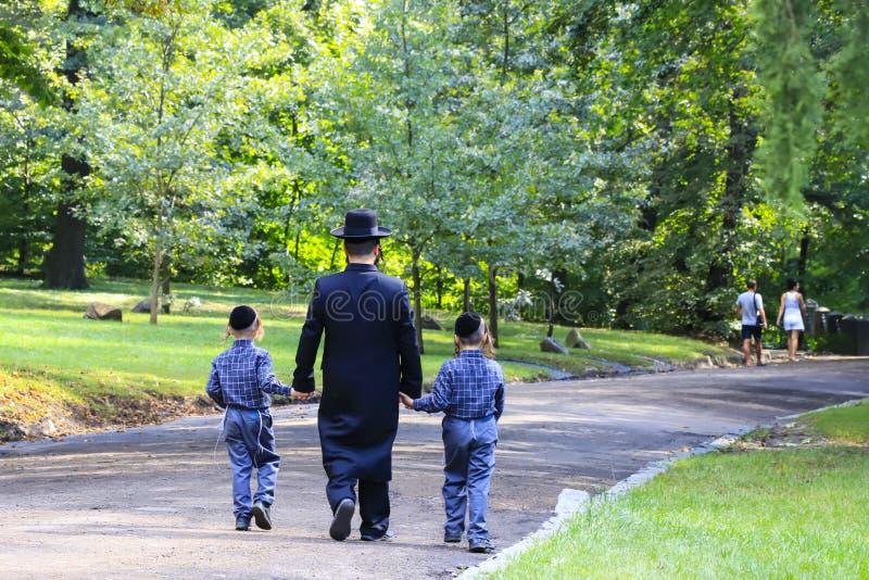 Religiöser Jude Eine Familie von Hasidic Juden, ein Mann mit Kindern, Wege durch Autumn Park in Uman, Ukraine, jüdisches neues Ja stockfotos