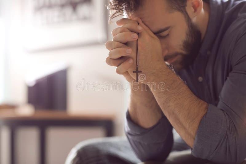 Religiöser junger Mann, der zu Hause zum Gott betet lizenzfreie stockfotografie