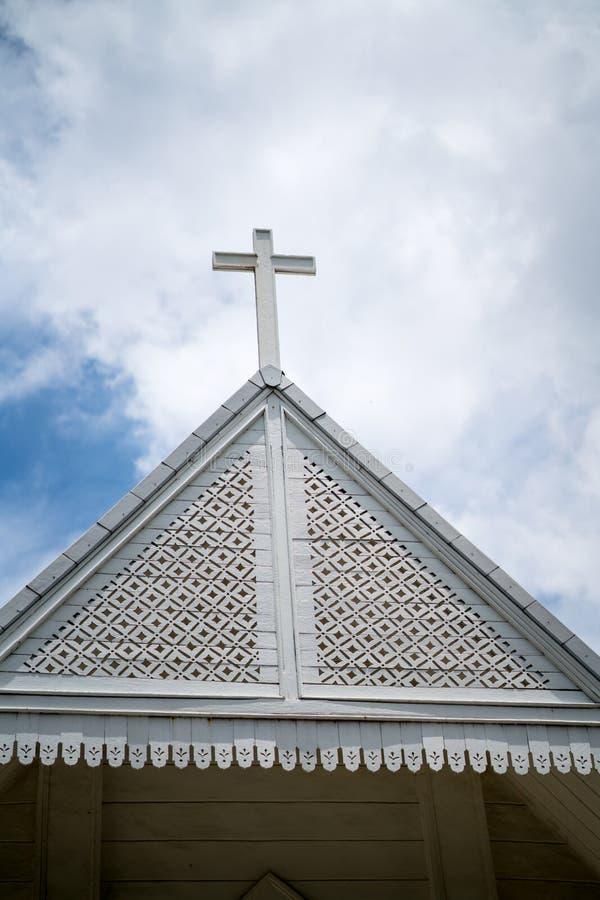 Religiöses weißes hölzernes Kreuz auf dekorativer Kirchendachspitze lizenzfreie stockfotos