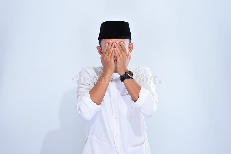 Religi?s asiatisk muslim man i traditionell kl?nning som ber och g?r dua, asiatisk muslim man att b?ra det traditionella skallelo royaltyfri foto