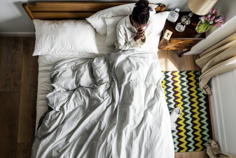 Religijna amerykanin afrykańskiego pochodzenia kobieta na łóżkowym modleniu zdjęcie royalty free