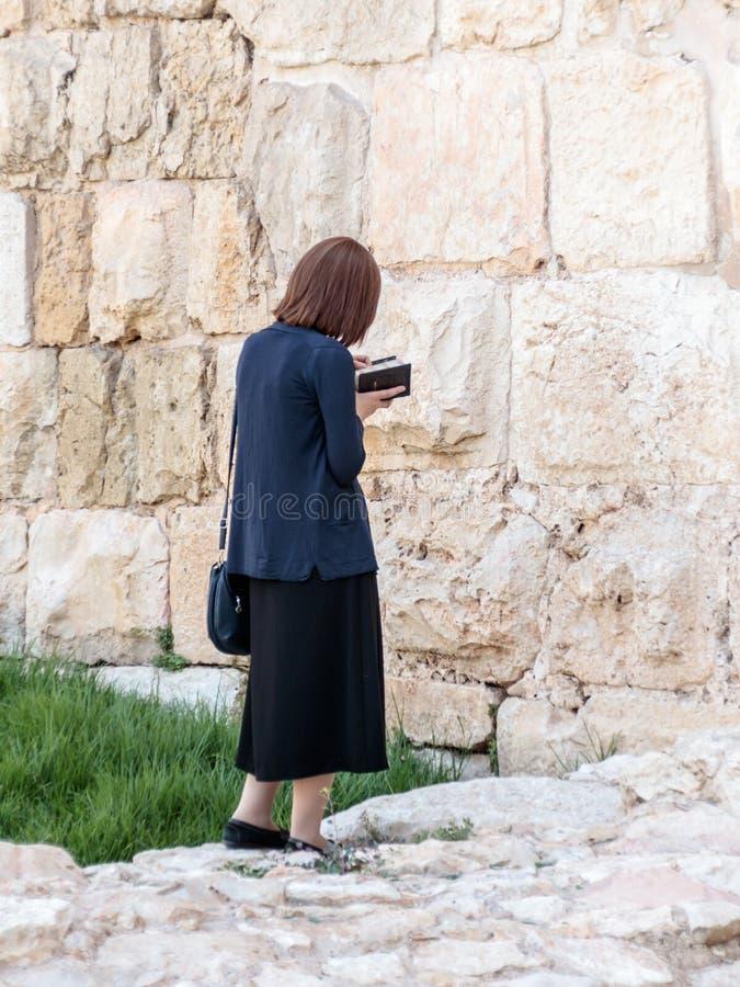 Religijna Żydowska młoda kobieta czyta książkę z modlitwami na zewnątrz fortecznych ścian stary miasto Jerozolima, Izrael obraz royalty free