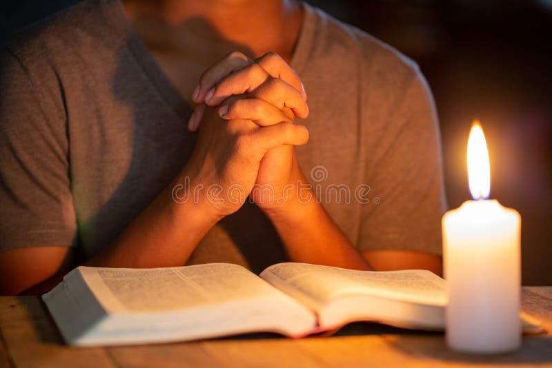 Religijni pojęcia młody człowiek one modlili się na biblii w pokoju i zaświecali świeczki iluminować zdjęcia royalty free