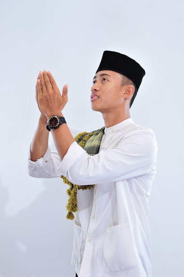 Religijny azjatykci muzułmański mężczyzna w tradycyjnym smokingowym ono modli się i robi dua, Azjatycka muzułmańska mężczyzna odz fotografia royalty free