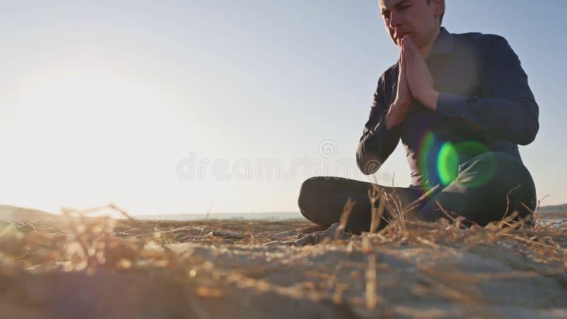 Religion Équipez se reposer de prière au sol à la religion de silhouette du soleil de coucher du soleil photo stock