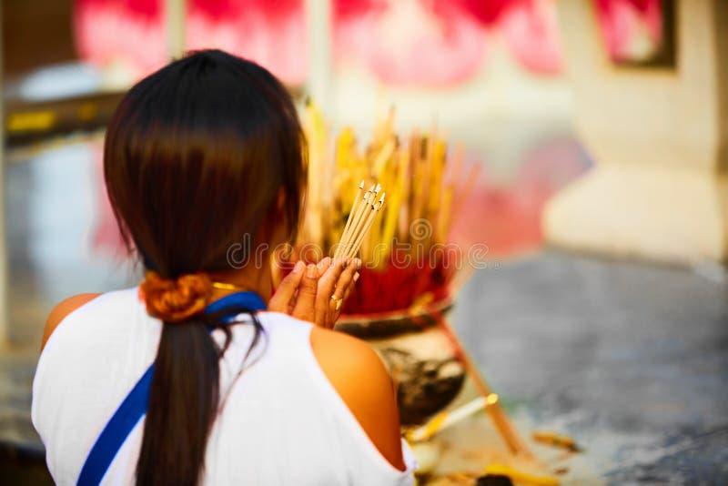 Religion Be Buddha för kvinna som rymmer rökelsepinnar på templet arkivfoton