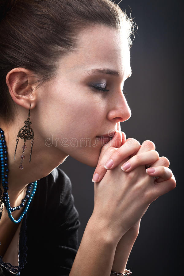 Religion concept - woman and her prayer. Over black royalty free stock photo