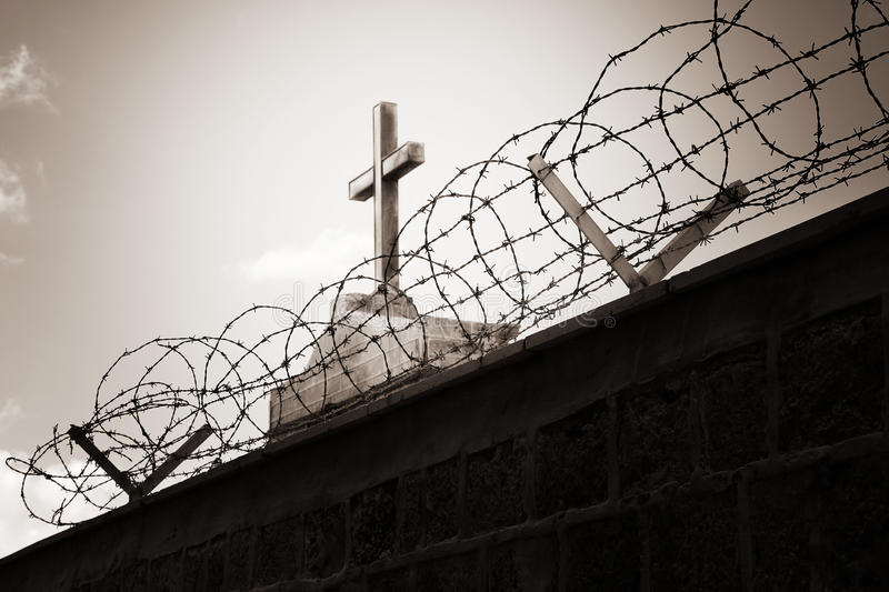 Religion and war - cross behind barbed wire. Religion and war concept - cross behind barbed wire stock photos