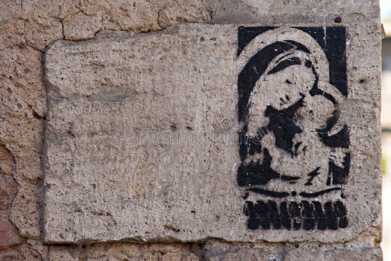 Religiongrafitti av Madonna med barnet på väggen, Rome royaltyfri foto