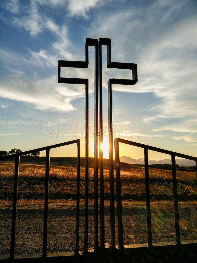 Religions. Symbols. Christian Cross in backlight. A stylized representation of the Calvary in a metallic gate royalty free stock photography