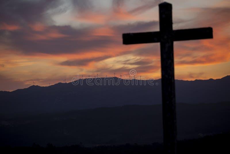 Religiontema, katolikkors och solnedgång royaltyfria bilder