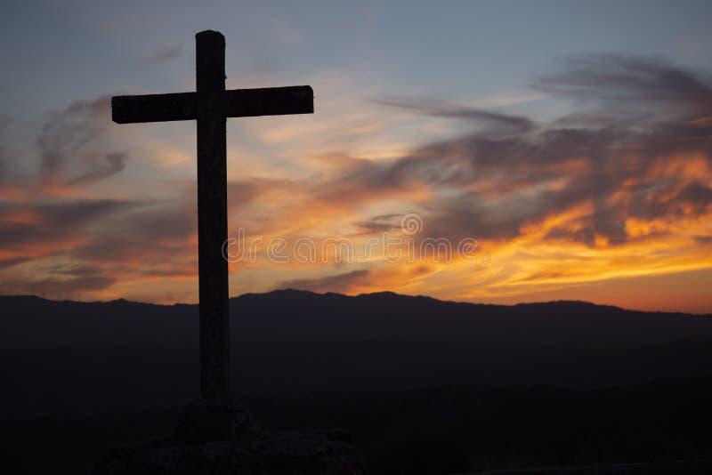 Religiontema, katolikkors och solnedgång royaltyfri bild