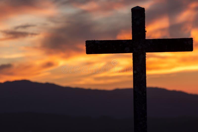 Religiontema, katolikkors och solnedgång fotografering för bildbyråer