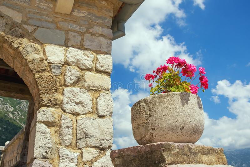 Stone flowerpot with flowers against the blue sky. Ancient Church of Our Lady of the Rocks, Montenegro. Religious architecture, details. Stone flowerpot with stock photography