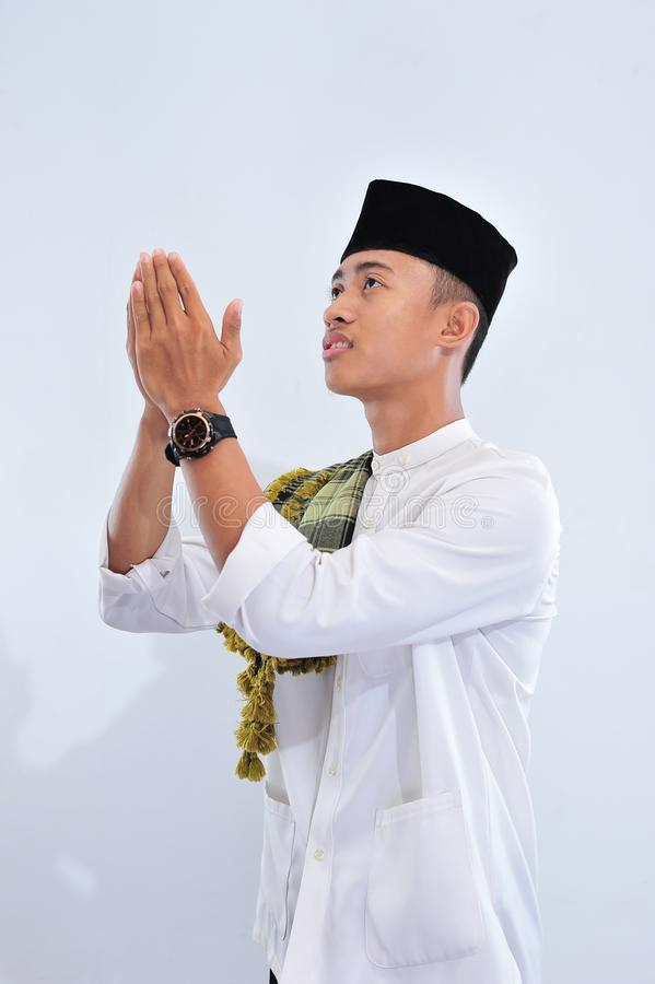 Religious asian muslim man in traditional dress praying and making dua, Asian muslim man wear traditional skull cap of indonesia royalty free stock photography
