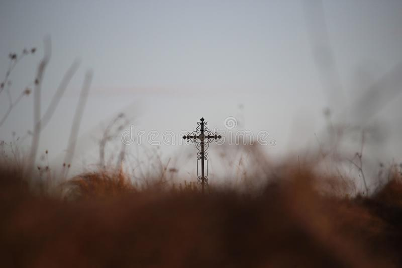 Religious background with blurred brown autumn grass and a cross further on. stock photo
