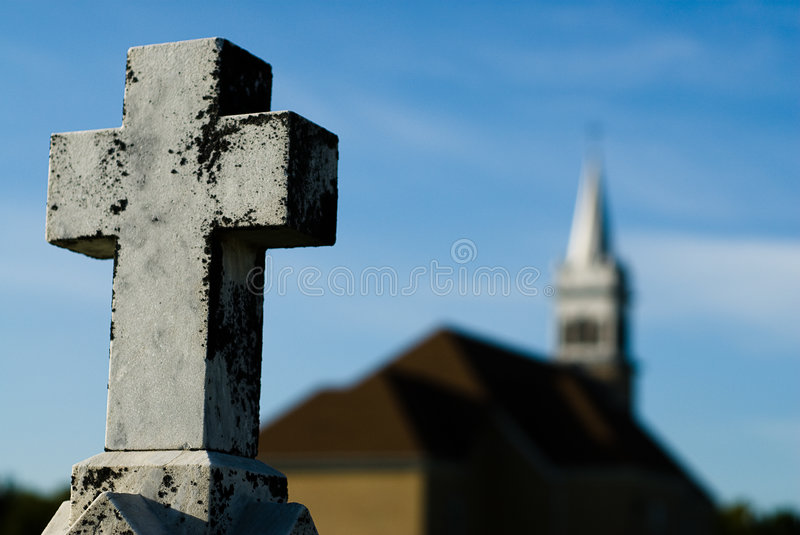 Religious Crucifix. Shallow depth of field view of a crucifix with a church in the background stock photography