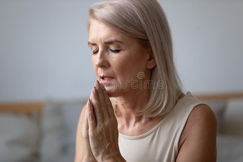 Religious faithful middle aged woman praying alone at home stock image