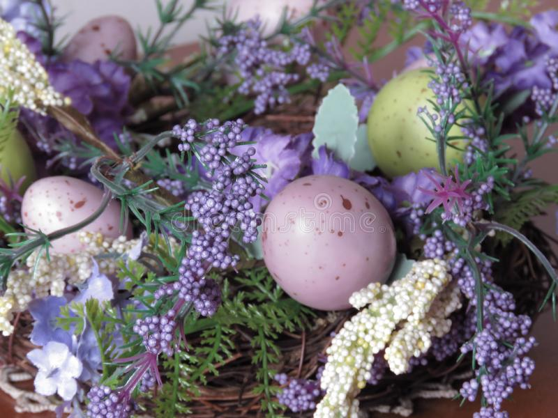 Religious Festivals and Traditions. Easter nest shaped basket of green blue purple flowers and colorful eggs. Easter home decoration. Quail Easter eggs. Easter royalty free stock photo
