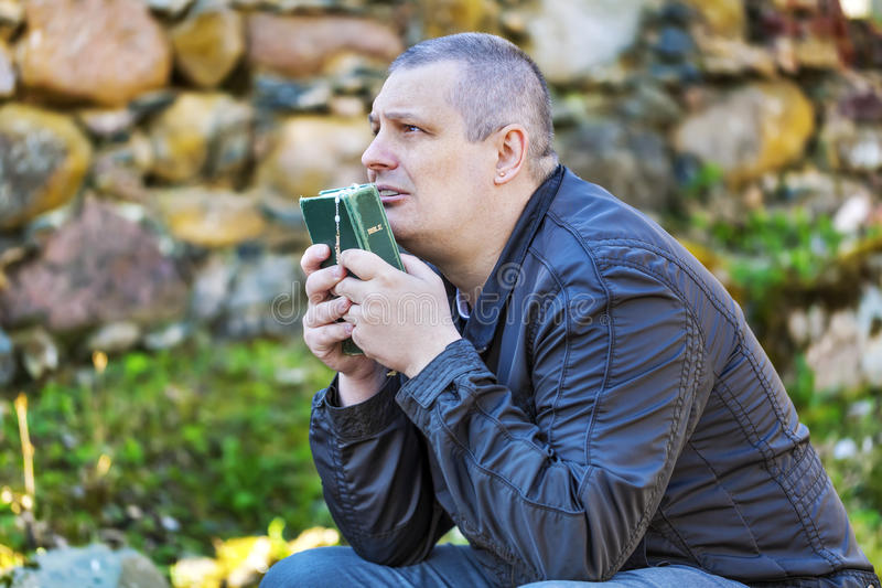 Religious man with Holy Bible and Rosary at Place of Worship stock images