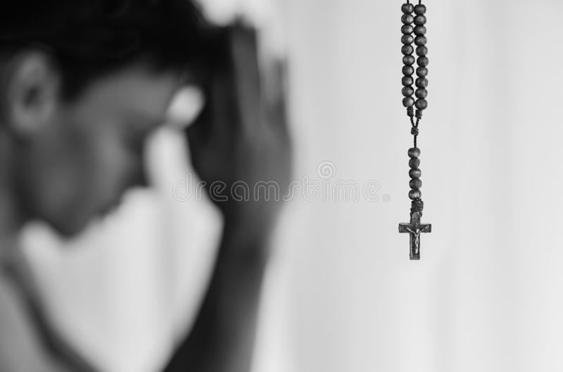 Religious man in prayer with his rosary cross neckalace, at hime. royalty free stock photos