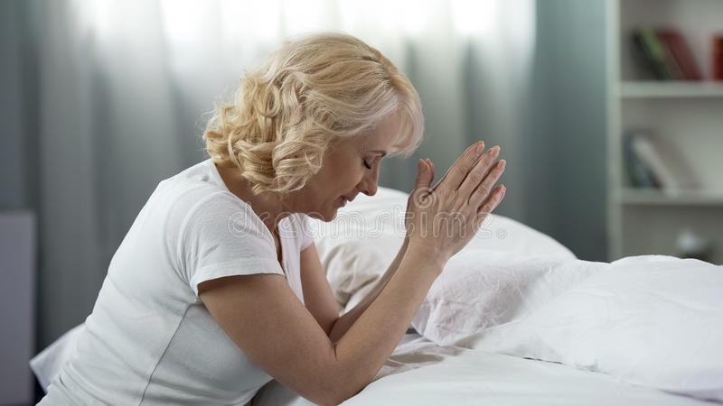 Religious mature woman sitting near bed with clasped hands and praying, peace stock image