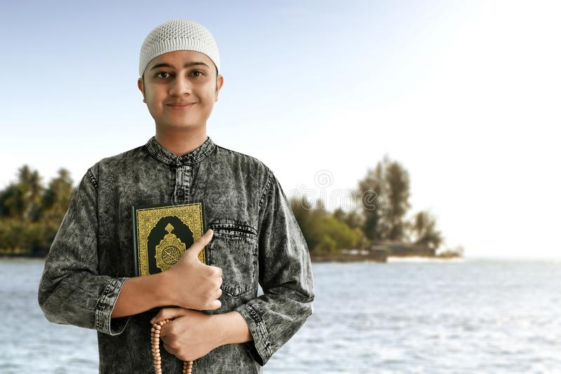Religious muslim man holding quran and rosary beads. Religious muslim man hold quran and rosary beads stock photos