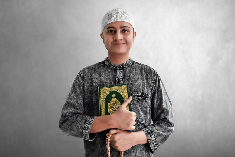Religious muslim man holding quran and rosary beads. Religious muslim man hold quran and rosary beads royalty free stock image